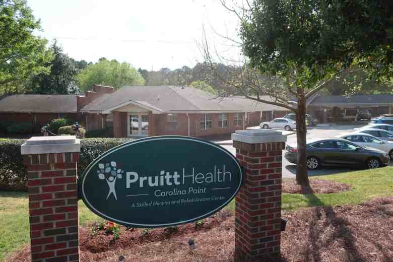 A skilled nursing facility sign is in the foreground and a building is in the background. The facility, A PruittHealth skilled-nursing facility in Orange County, is dealing with an outbreak of COVID-19, and has a history of poor staffing.