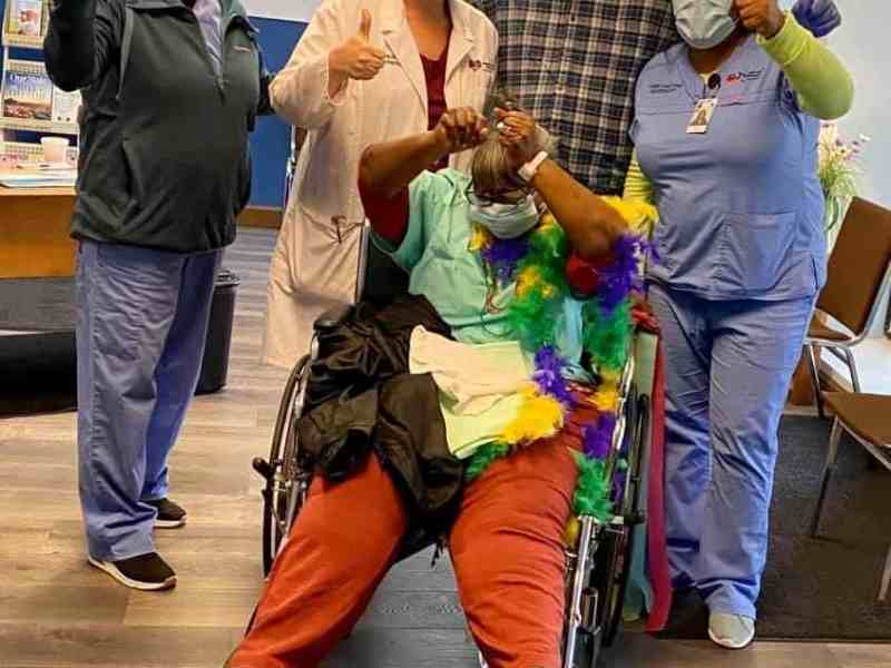 A patient in a wheelchair is cheering, around her medical providers and family members do a thumbs up. The patient recovered from coronavirus at a hospital in eastern North Carolina. Another hospital system in the region, vidant health, is experiencing financial difficulties because of coronavirus
