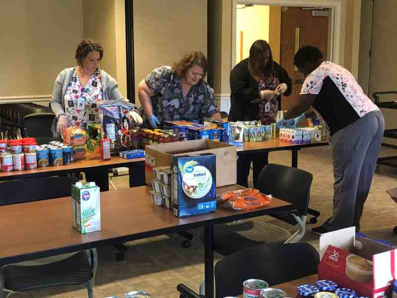Hospice workers set up a food pantry on tables in what looks like a conference room.