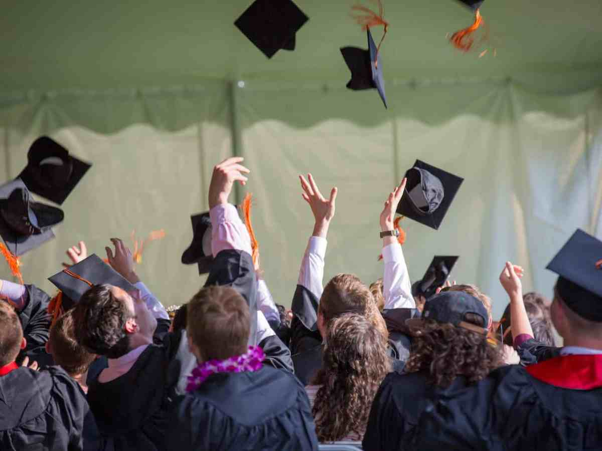 photo shows young graduates throwing up their mortarboards