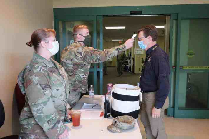 two people in fatigues use a infrared thermometer to check the temperature of a third person outside a set of doors into a COVID surge facility