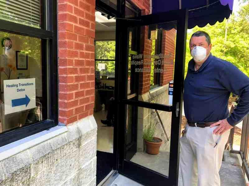 man in mask opening door
