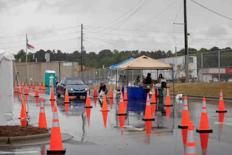 We see a tent amid cones that are directing cars into a line. The tent is for testing people for COVID-19