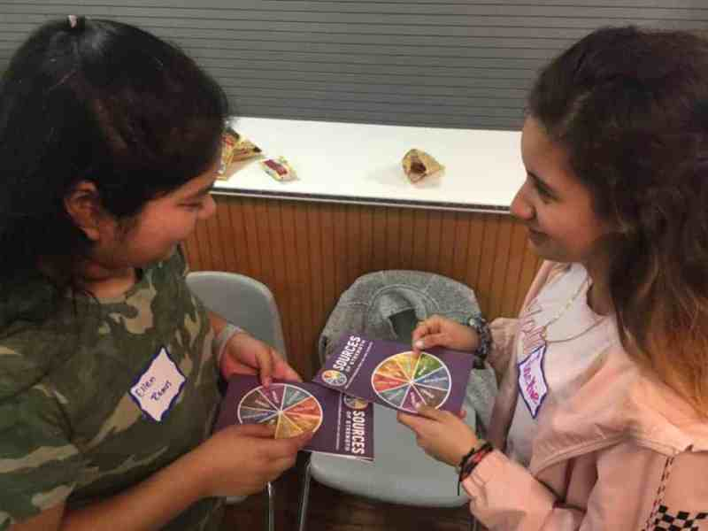 Students holding colorful cards in a program about suicide prevention