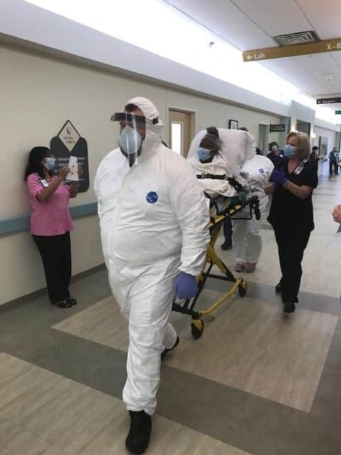 People in wearing masks are wheeling a masked patient down a hospital hallway. The patient is recovering from coroanvirus