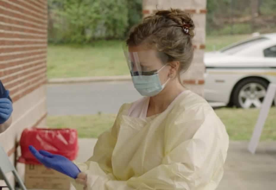 shows a woman putting on her personal protective equipment as she prepares to test someone for COVID