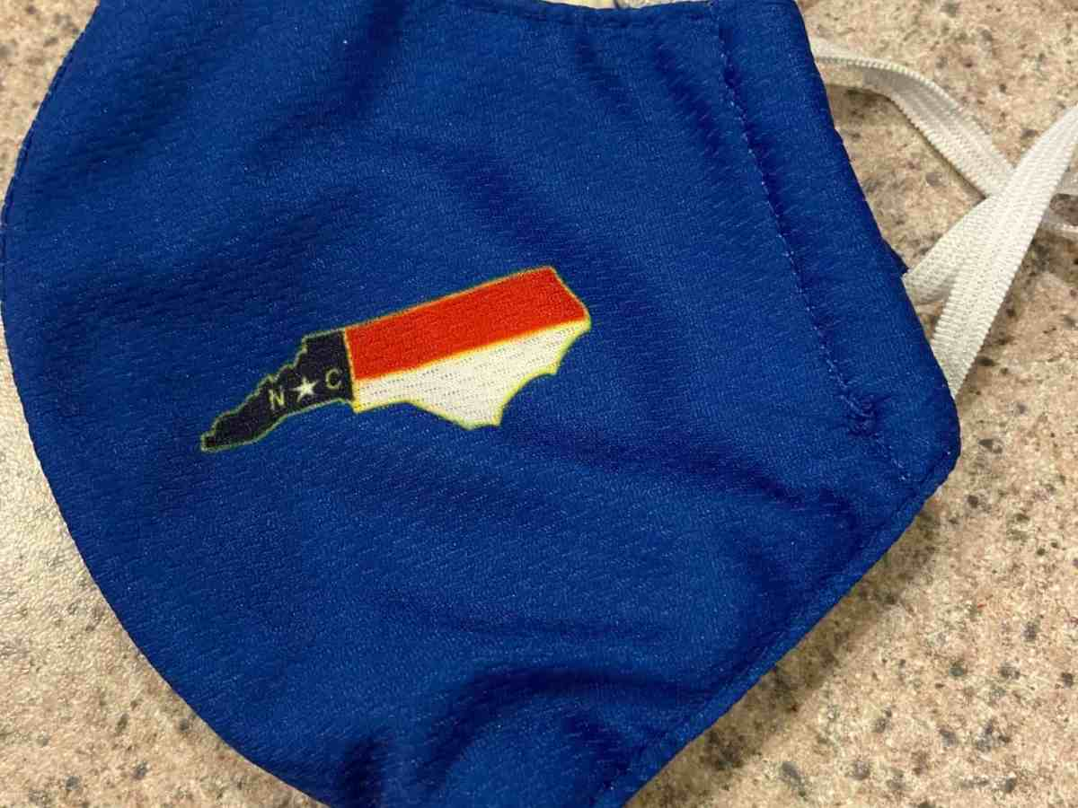 shows a facemask used to prevent COVID 19 transmission. It's blue with an outline of the state of North Carolina with the flag colors inside the outline
