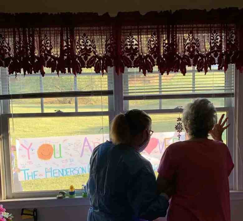 """A Cherry Springs resident and staffer look outside a window at a """"You Are Loved"""" sign placed in the grass outside the facility. They do so from the resident's room, where she has been quarantined since a COVID-19 outbreak began in the facility, where a strike team functioned to keep the outbreak under control."""