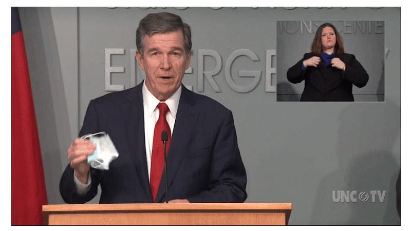 shows a man at a podium holding up a face mask used as a COVID preventive as he speaks from behind a podium.
