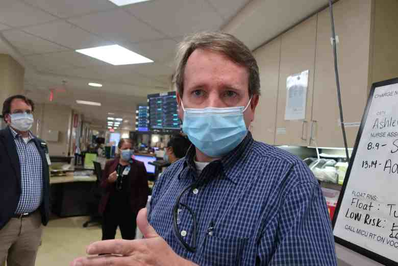 a man in a mask worn against COVID looks at the camera. He's standing in a hospital ward.