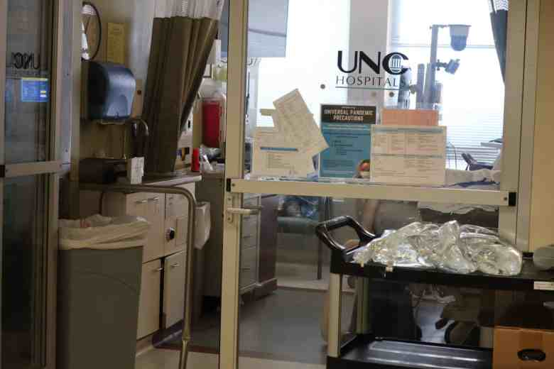 Shows the windowed wall of an ICU room containing a COVID patient. You can only see the patient's feet.