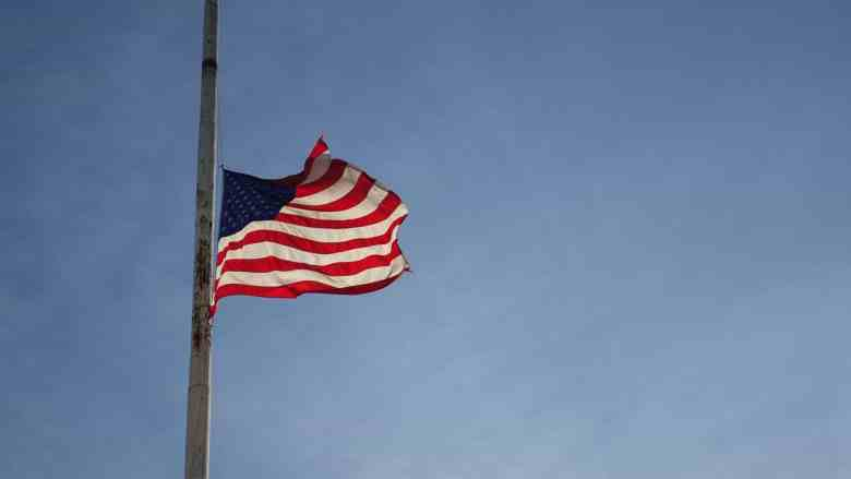 photo shows a clear blue sky with an American flag flying at half-mast, in honor of the hundreds of North Carolinians lost to coronavirus so far