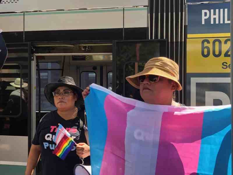 We see a demonstrator in a tan hat holding a large transgender flag and another person behind them in glasses and a black hat holding two smaller flags, the pride flag and the transgender flag, at a rally for transgender rights on a train platform in Phoenix, Arizona.