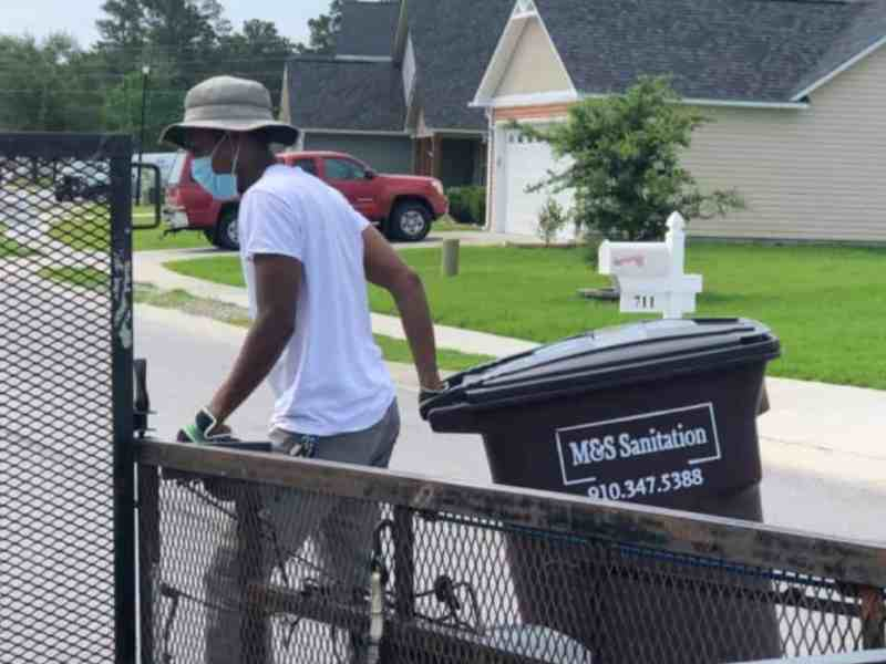 Photo shows a young Black man in a hat and mask placing a garbage can in a driveway. Sanitation workers face the daily effects of coronavirus.