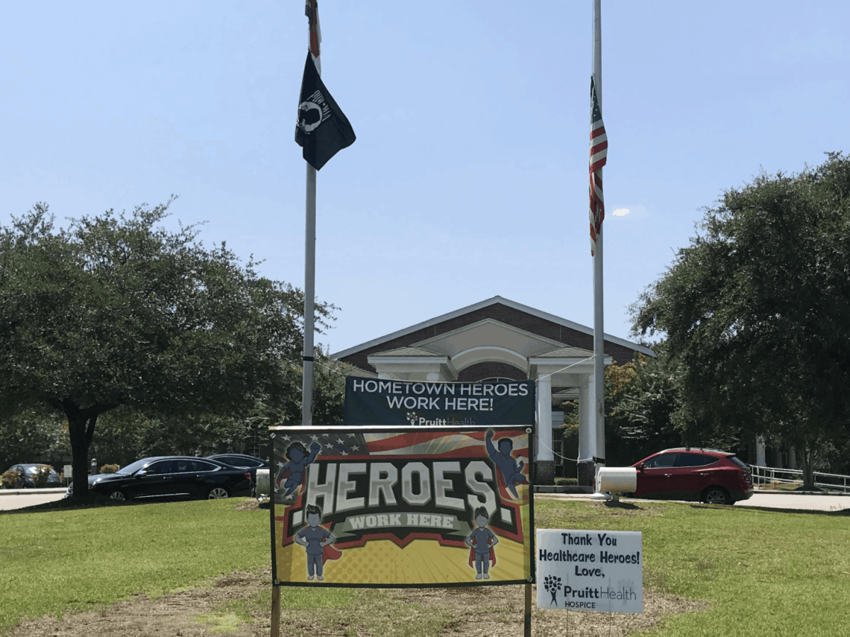"""shows the front of a building with several flags on poles, the American flag is at half staff, as there are dead COVID patients within. A sign in front of the building reads, """"Heroes work here"""""""