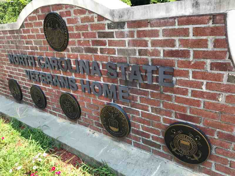 """Shows a brick wall with the title, """"North Carolina State Veterans Home"""" and brass plaques on the wall from each of the branches of the U.S. military"""