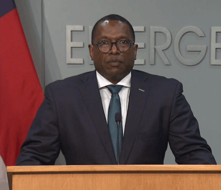 shows a handsome African American man in a suit standing at a podium and looking straight at the camera