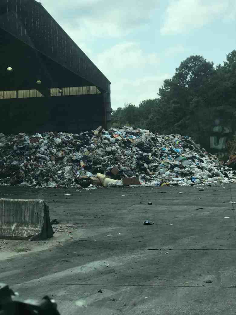 shows a large building like a warehouse that is open on one side. A pile of collected garbage spills out of the side.