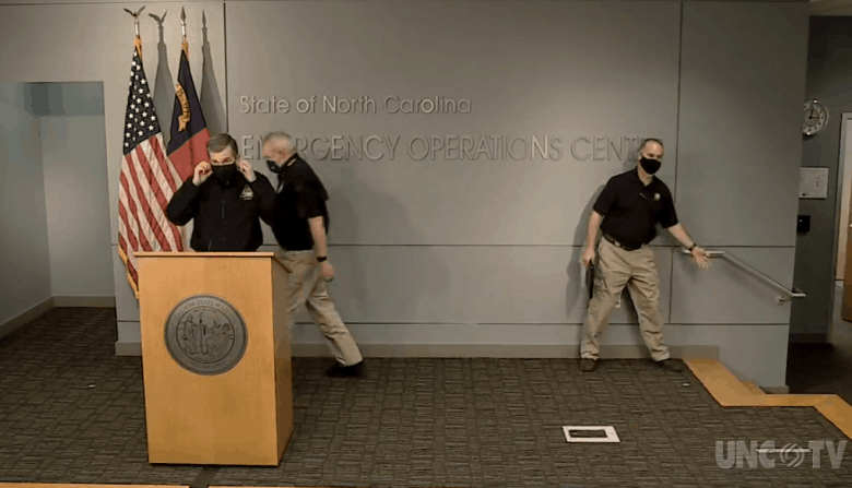 shows men clad in emergency operations shirts and face coverings arrivinng on a stage