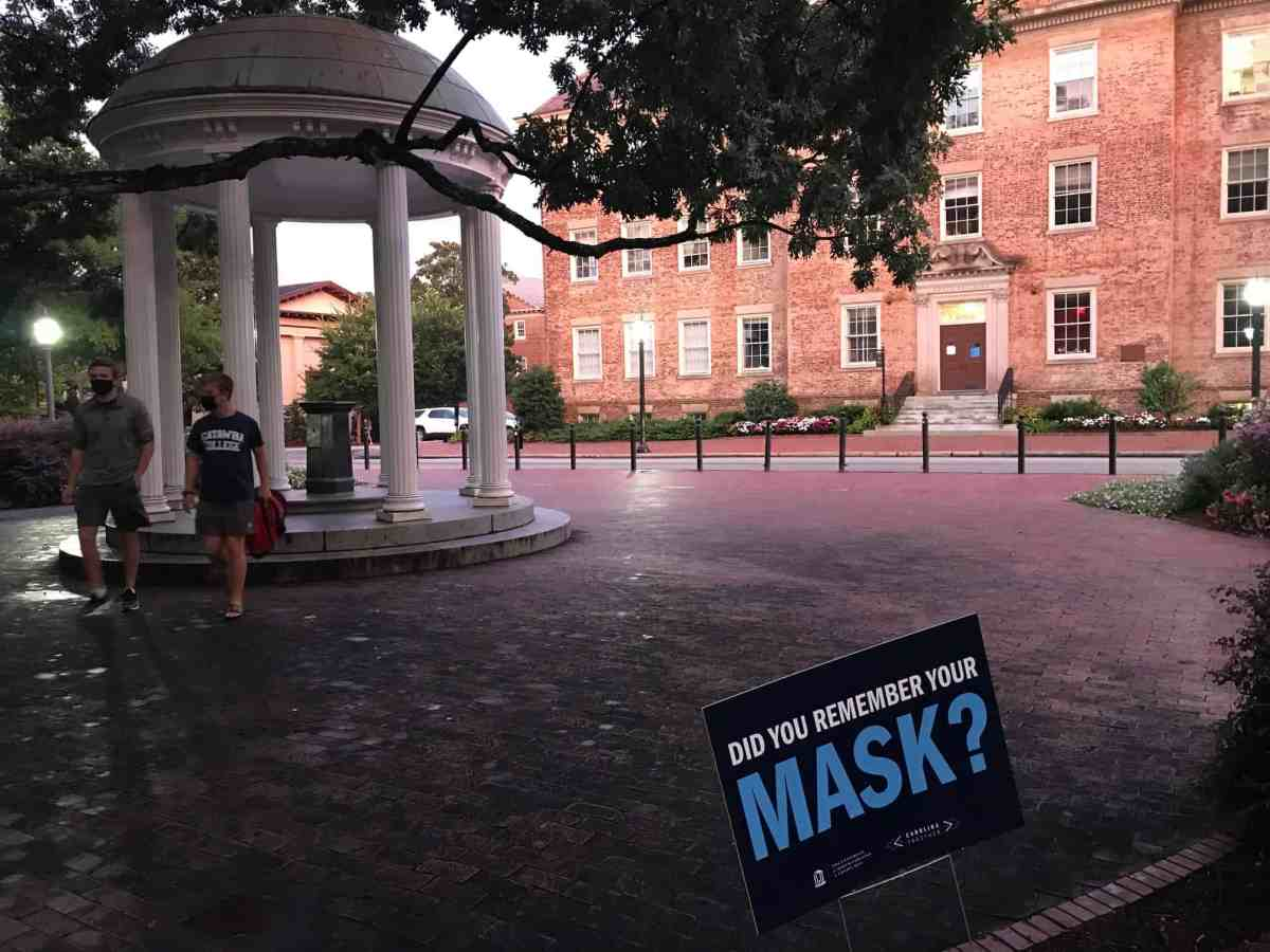 """shows a sign reading, """"Did you remember your MASK?"""" in the foreground, in the background is the iconic Old Well on the UNC Chapel Hill campus, two young men in masks walk by."""