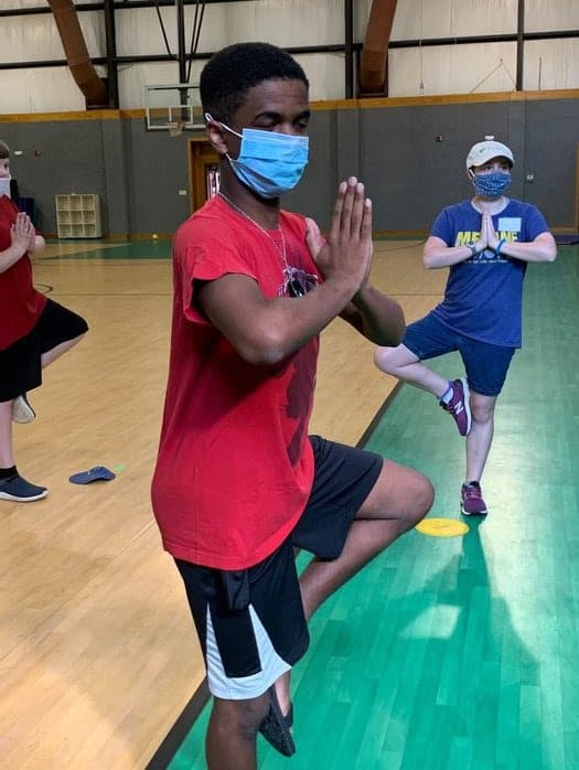 shows a young man doing a yoga pose, others in the background do the same. They're all wearing face masks against COVID