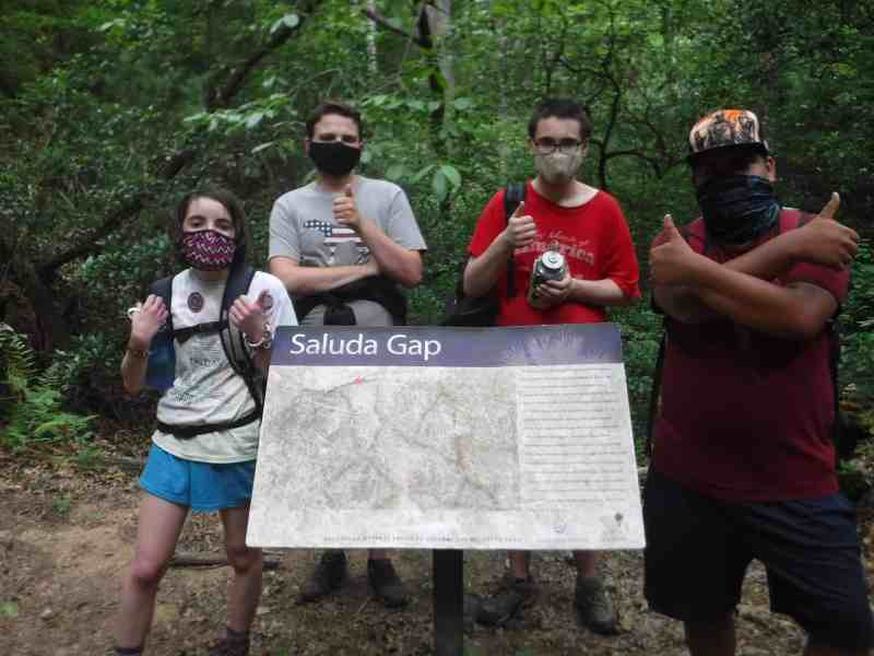 shows a group of young people at a trail head, they're all wearing masks against COVID