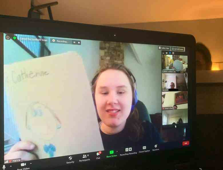 shows a computer screen with a young woman who's wearing headphones holding up a drawing. The young woman was attending a virtual camp because of COVID