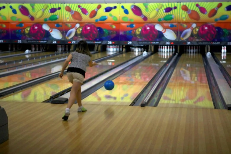 shows a woman throwing a bowling ball down the wooden alley with a colorful wall in the background