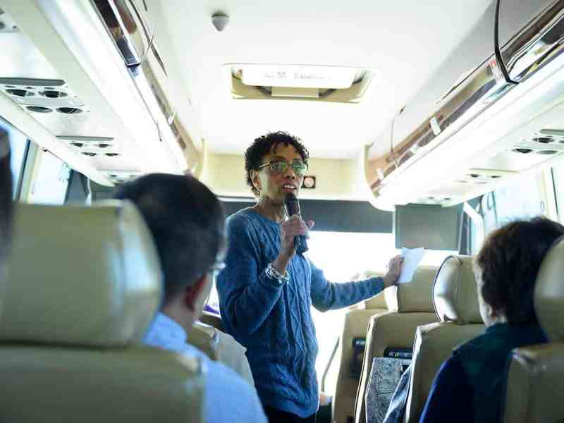 A woman with short black hair speaks to a bus full of students with a microphone. She is Dr. Pam Ries of the ECU college of nursing. She heads a rural health program.