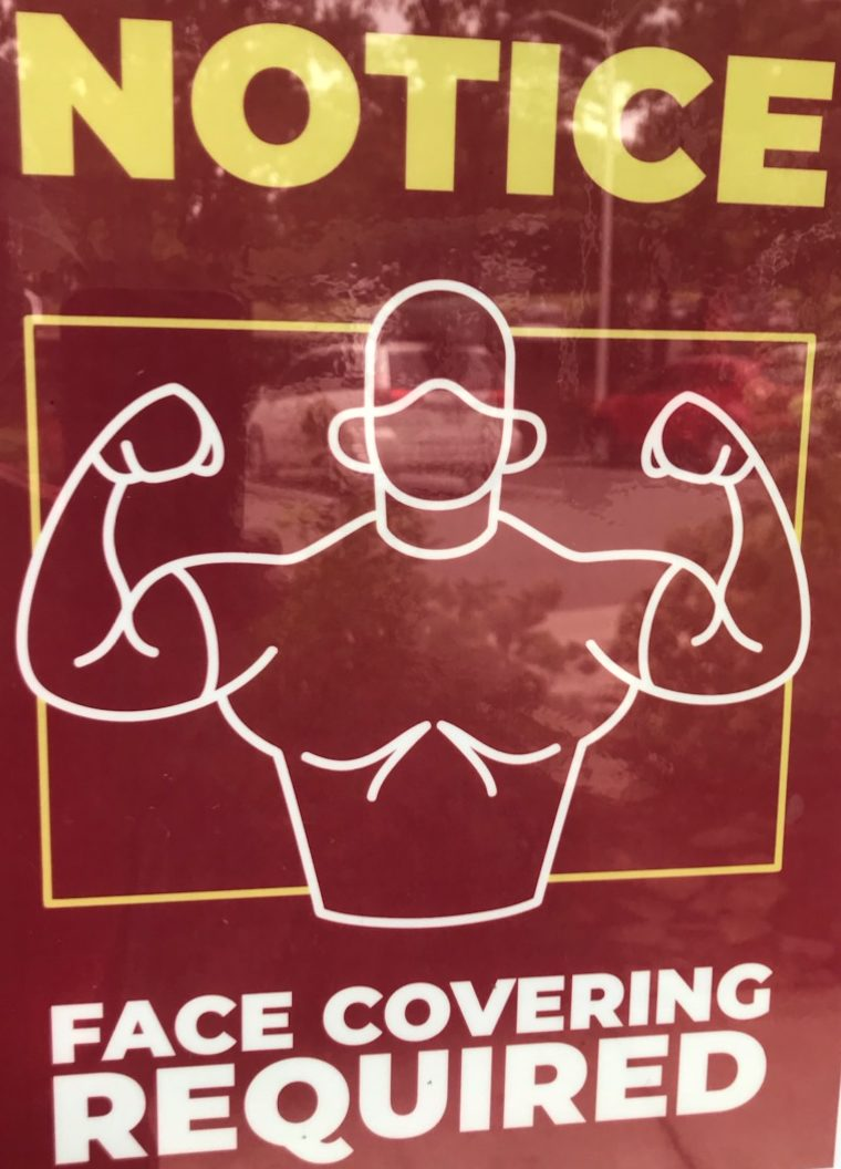 Red sign with yellow and white lettering and drawing of muscly man wearing a face mask