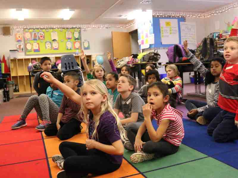 shows a group of children sitting in a brightly colored classroom, their attention is (mostly) on the front of the room