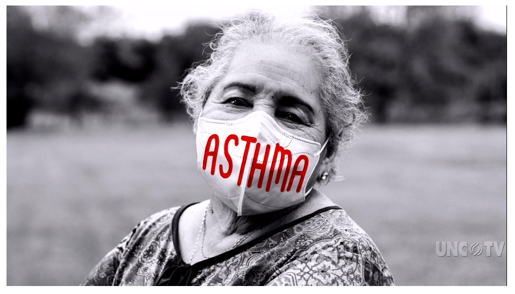 shows an older woman standing outside, wearing a mask against COVID, her mask reads: Asthma