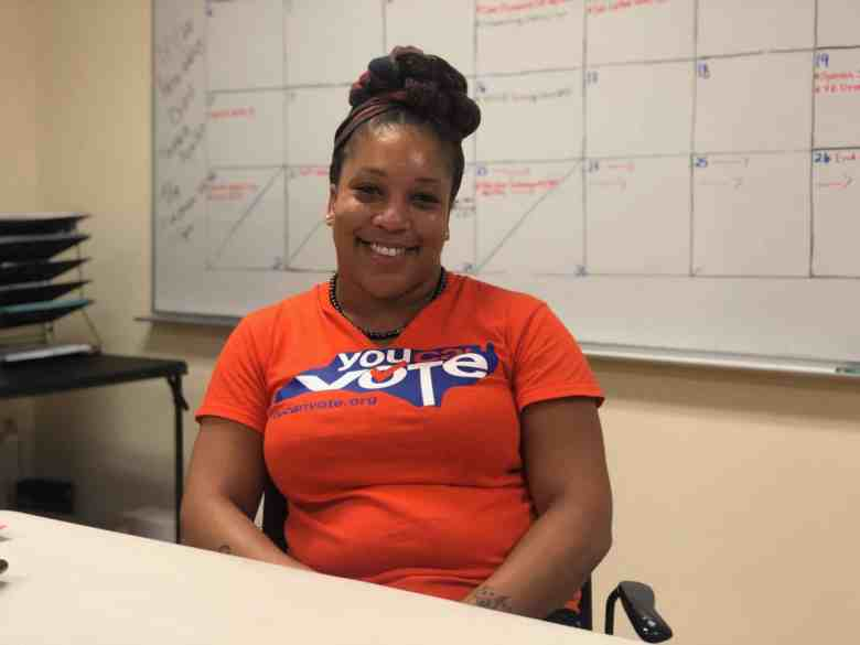"""We see Zion Lemelle, organizing director for You Can Vote, smiling at the camera wearing an orange """"You Can Vote"""" shirt at the organization's office."""