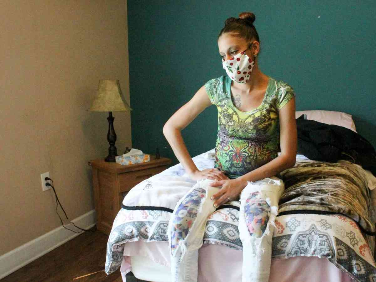 A pregnant woman with a mask sits in her room.