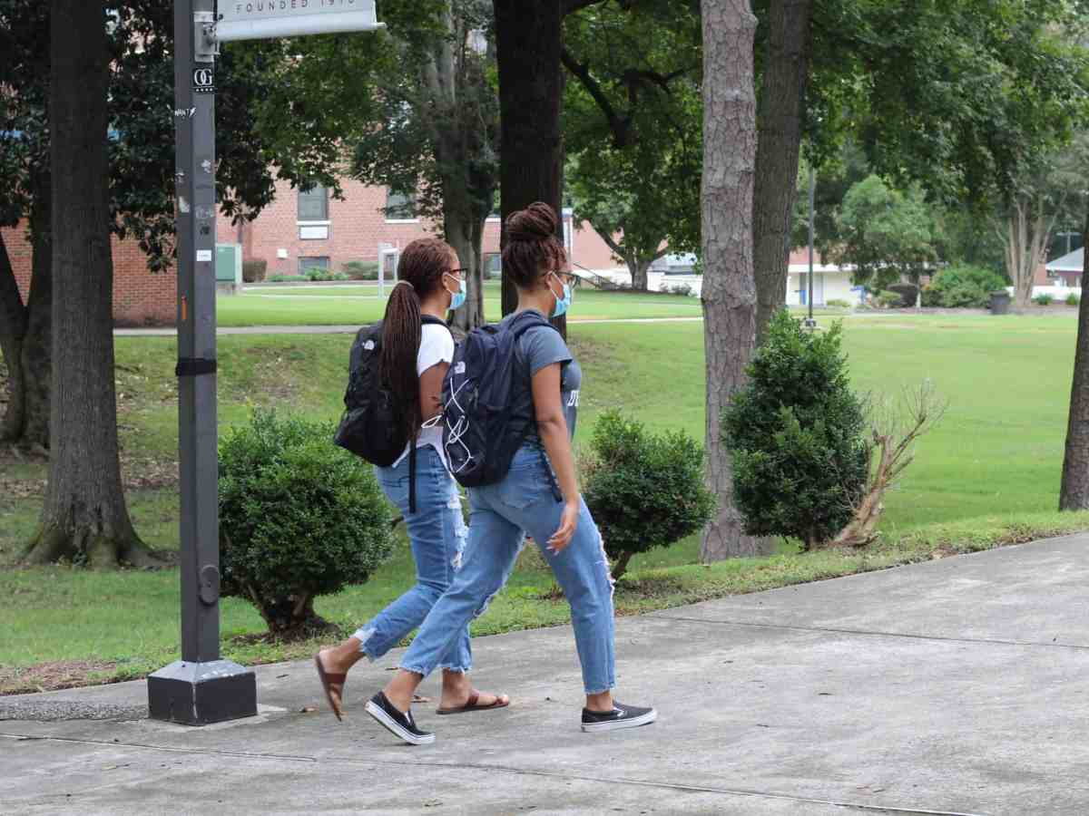 two young Black women wearing jeans, t-shirts and backpacks walk down a sidewalk bordering a green, tree-filled space on NCCU's campus