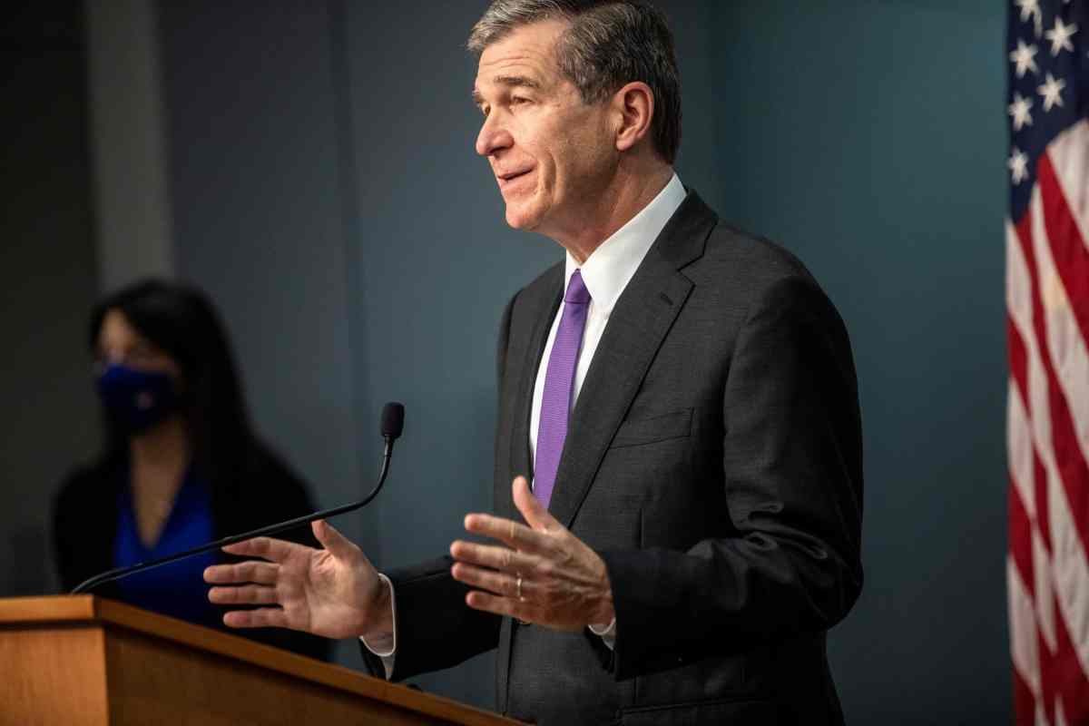 shows Cooper standing at a podium in a purple tie, gesturing with his hands, during a COVID briefing on Nov 5