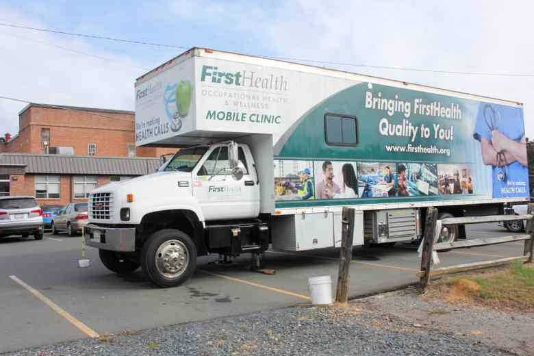 A mobile clinic van is parked in front of a red brick building