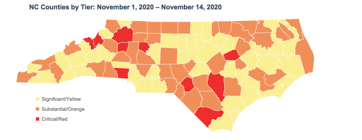 shows a map of North Carolina with many counties colored in yellow, some counties colored in orange and a handful of them red, to denote critical levels of COVID activity