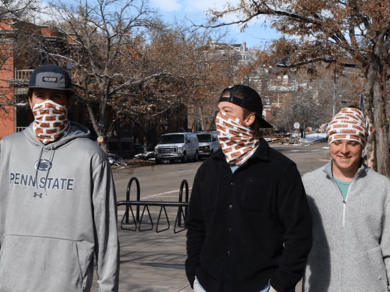 shows three young people waring face coverings to prevent them from spreading COVID