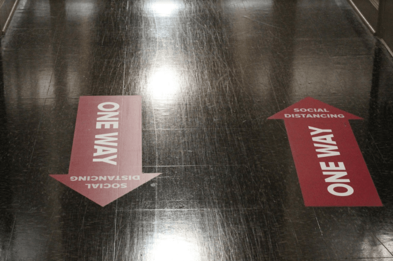 photo shows a black floor with red arrows marking which way students should walk