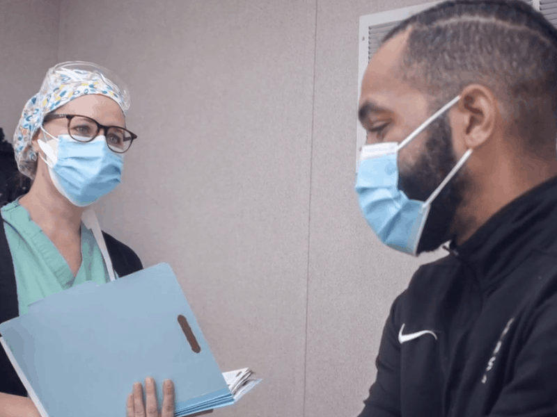 shows a health care provider in a mask holding a folder talking to a patient who's als in a mask.