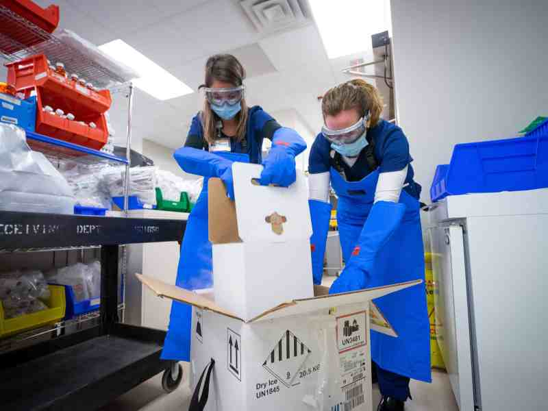 shows two women in aprons, gloves, masks and goggles opening up a cardboard box filled with vaccines