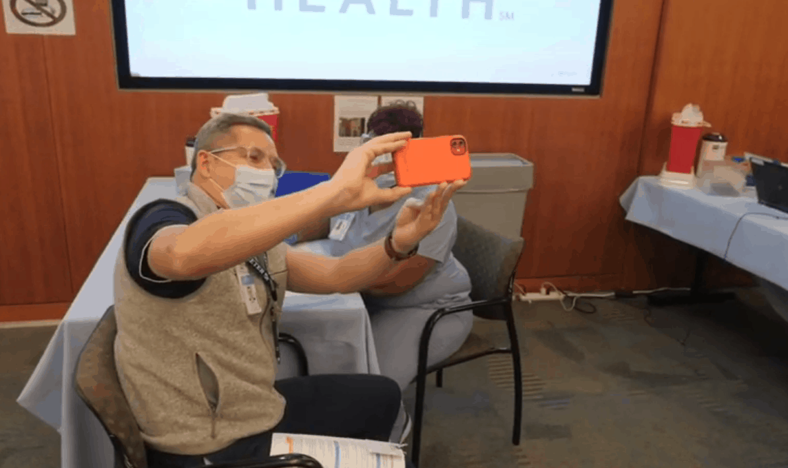 a man wearing a mask holds up his smart phone to take a photo as he receives a COVID vaccine shot