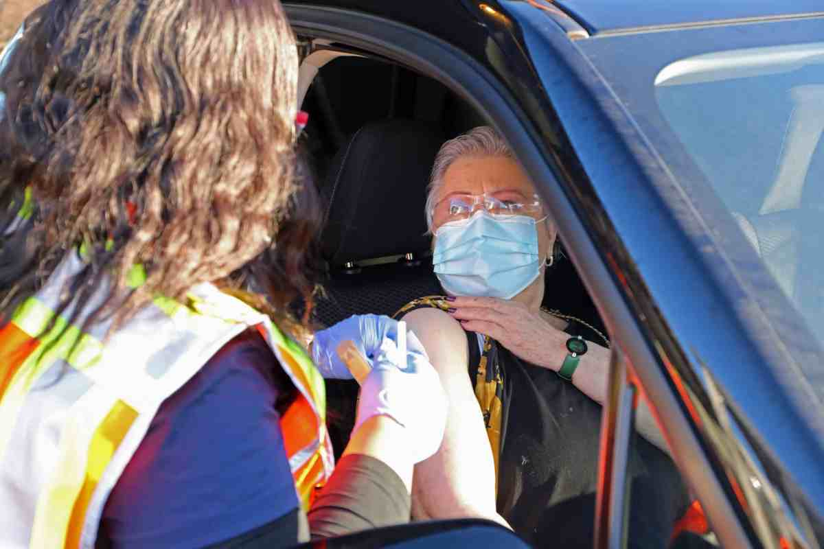 shows a woman sitting in a car getting a shot. She's wearing a mask to prevent transmission of COVID-19