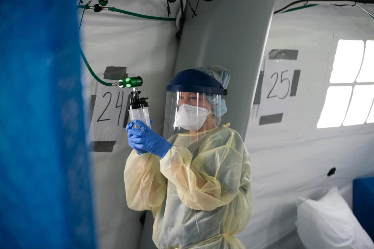 A woman in full medical gear stands in a tent and holds a bottle.