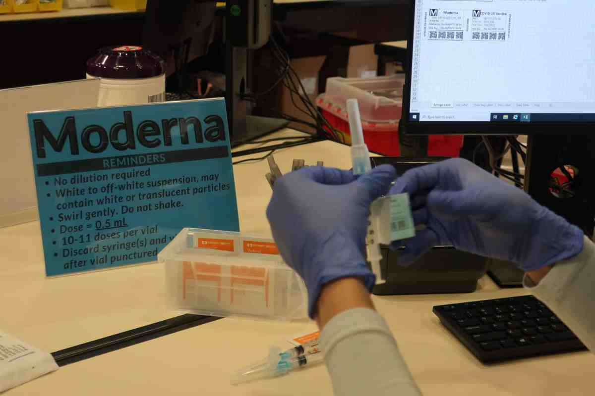 """shows a pair of gloved hands handling a syringe of COVID vaccine, there's a sign beyond the hands that reads """"MODERNA"""" in large letters"""