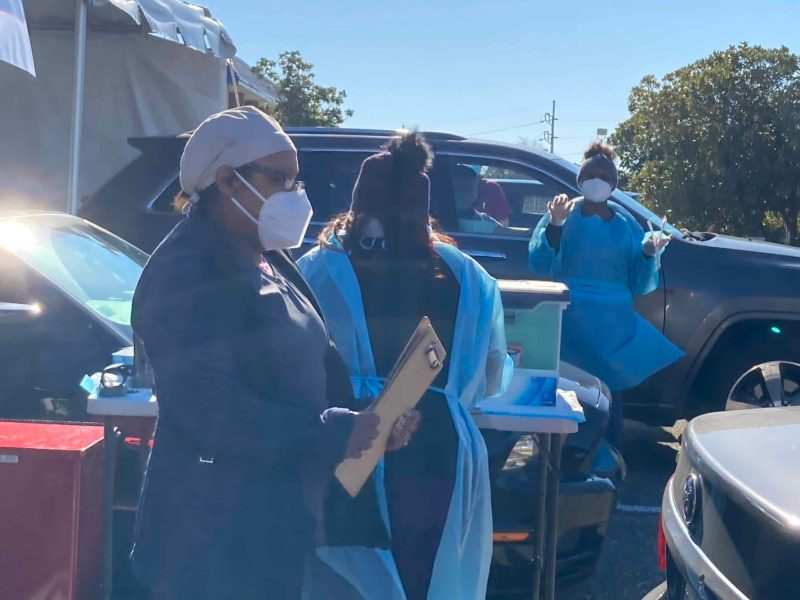 Health care workers at a COVID-19 drive-thru site in Fayetteville prepare to administer rapid antigen tests. Photo credit: Greg Barnes