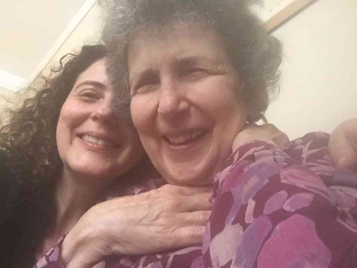 We see Ester Amy Fischer hugging her mother while they take a selfie. Her mother Barbara, who wears a purple shirt with spotted patterns, is smiling with laughter.