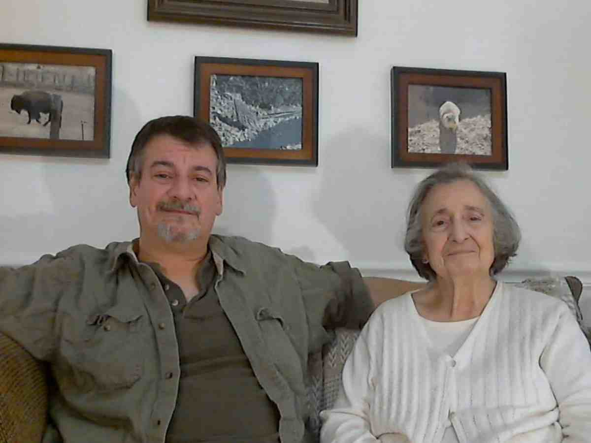 We see Mark Newton sitting with his arm around his older mother on a brown corduroy couch in their home in Reidsville. Both smile, with closed teeth, and look at the camera.