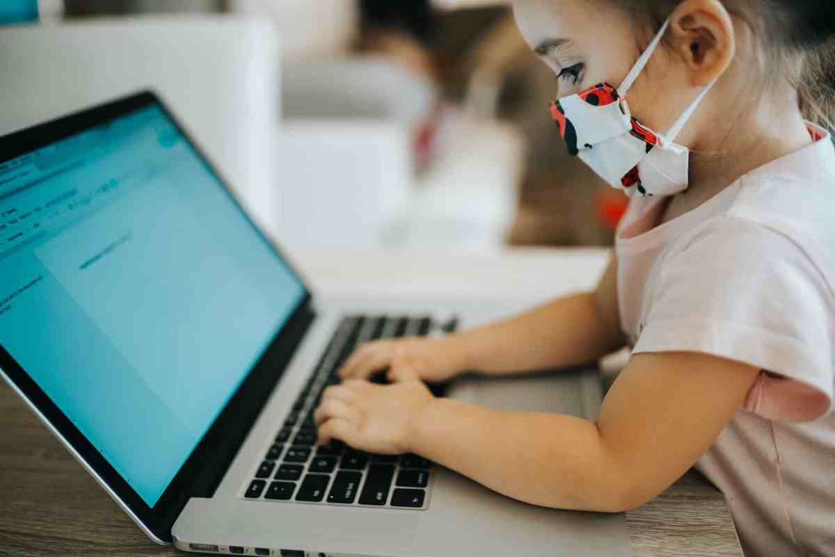 little girl with a mask on to prevent COVID works at a laptop